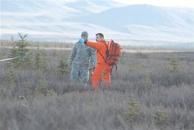 A Canadian search-and-rescue technician points out the causality collection point to a soldier role-playing a wounded crash victim at Donnelly Training Area, Alaska, Oct. 30, 2013. The soldier is part of a Joint Task Force Alaska, Alaska National Guard, U.S. Army Alaska, Canadian Joint Operations Command arctic search-and-rescue exercise at Fort Greeley and Joint Base Elmendorf-Richardson, Alaska. U.S. Army photo