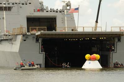 NASA engineers, Navy divers and Sailors assigned to the amphibious transport dock ship USS Arlington (LPD 24) tow a test Orion capsule into the well deck of Arlington. This phase one test determined the best method for recovering the capsule after earth reentry and splashdown in the ocean. (U.S. Navy photo by Chief Mass Communication Specialist James Davis/Released)