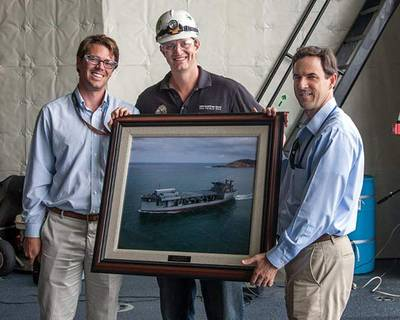NASSCO Program Manager William McKay and Area Manager Aaron Rockwell present the ship's captain, Jonathan Olmsted, with a photo of the MLP 3 AFSB, USNS Lewis B. Puller. (Photo: NASSCO)