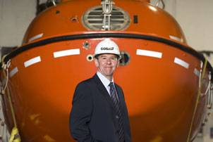 New Cosalt Offshore General Manager Colin Cunningham with a lifeboat supplied by the company. Photo courtesy Think PR ( Scotland) Ltd
