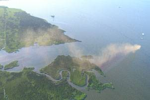 Pictured here is an aerial photo of smoke billowing from a wellhead after a towing vessel's dredge barge allided with the structure in Barataria Bay, La., as the vessel and barge exited Mud Lake, July 27, 2010. The barge was en route to the towing vessel's facility in Berwick Bay when the incident occurred. More than 150 response personnel and 31 boats responded to a mixture of oil and gas emanating from the wellhead. Official U.S. Coast Guard photo