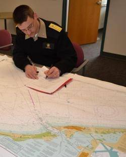 Rear Adm. Gerd Glang certifies a new print-on-demand chart agent after inspecting the company's sample chart. (Photo: NOAA)