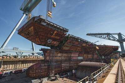 The 780-ton upper bow unit was lowered into the dry dock on Wednesday and placed on the aircraft carrier John F. Kennedy (CVN 79). (Photo by Ashley Cowan/HII)