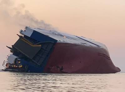 The stern view of the Golden Ray six hours after the heeling event. Flame and smoke emanate from cargo decks on the starboard side of the vessel. (Photo courtesy of the U.S. Coast Guard)