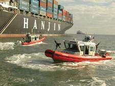 Two Coast Guard small boats set a security zone around the 900-foot container ship Cosco Busan. (U.S. Coast Guard photo)