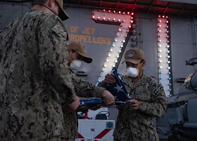 U.S. Sailors fold the American flag after evening colors on the flight deck of the aircraft carrier USS Theodore Roosevelt (CVN 71) April 24, 2020. (U.S. Navy photo by Kaylianna Genier)