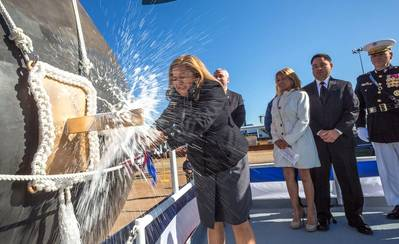 USS Rafael Peralta's sponsor, Rosa Maria Peralta, breaks a bottle of champagne against the vessel's bow (Photo: General Dynamics Bath Iron Works)