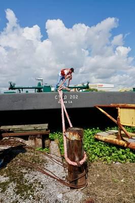 Баржа Cenac и работник трудно на работе на внутренних реках. КРЕДИТ: Сенак