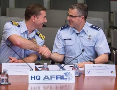 अमेरिकी तट रक्षक कैप्टन ग्रेग रोथ्रोक, कोस्ट गार्ड रिसर्च एंड डेवलपमेंट सेंटर कमांडिंग ऑफिसर, और एयर फोर्स मेजर जनरल विलियम कोलेली, वायु सेना अनुसंधान प्रयोगशाला कमांडर, 12 अप्रैल, 2018 को राइट-पैटरसन वायुसेना बेस, ओहियो में हाथ मिलाते हैं, उनके दो संगठनों के बीच समझने के ज्ञापन पर हस्ताक्षर किए जाने के बाद। समझौते पर यूएससीजी आरडीसी और एएफआरएल आपसी लाभ के कार्यों पर मिलकर काम करने की अनुमति देता है। (आरजे ओरीज़ द्वारा यूएस वायुसेना फोटो)