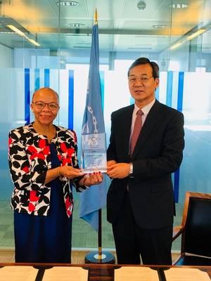 श्री मसाफुमी कुरोकी डॉ क्लियोपेट्रा डौम्बिया-हेनरी (फोटो: रेकाएप आईएससी) को प्रशंसा का एक स्मृति प्रदान करते हैं।
