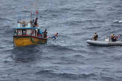 スリランカの漁師は、アレーバーク級の誘導ミサイル駆逐艦USSディケーター(DDG 73)から汽船を停止させた後、汽船に援助を提供するために停止した後、堅い船体のインフレータブルボートに飛び泳ぎます。 (米海軍の写真)