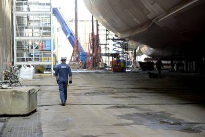 特拉华湾海岸警卫队的海洋检查员Ryt Thomas在2018年10月4日在费城造船厂建造的850英尺集装箱船Kaimana Hila下面行走.Kaimana Hila和Daniel K. Inouye是美国有史以来建造的两艘最大的集装箱船(Seth Johnson的海岸警卫队照片)