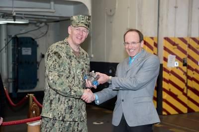 纽波特新闻造船公司的研发总监Don Hamadyk向海军海上系统司令部的首席工程师兼船舶设计,集成和海军工程副指挥官Lorin Selby赠送了第一个三维印刷金属部件。在USS Harry S. Truman(CVN 75)上。摄影:Matt Hildreth / HII。