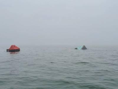 パピーのプライドの船尾は、テキサス州ガルベストンでの衝突後、船の膨張式救命いかだの横の喫水線の上に表示されます。沿岸警備隊の乗組員は、漁船とケミカルタンカーのボウフォーチュンが衝突した後、乗船している4人の乗組員のうち2人を探し続けています。 (ガルベストン基地による米国沿岸警備隊の写真)