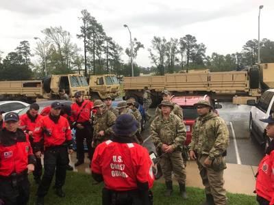 海上保安庁の乗組員は、2018年9月16日、ノースカロライナ州のハリケーンフィレンツェに対応して救助活動を行う前に、戦術について話し合っています。沿岸警備隊は被災地の州や地方の機関と協力しています。画像:USCG)