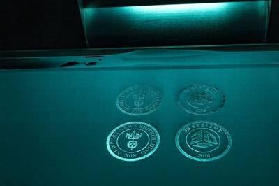 Logos von Newport News Schiffsbau und 3D-Systeme wurden während einer Vorführung des neuen 3-D-Druckers hergestellt. (Foto von John Whalen / HII)