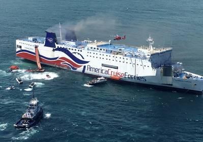 The Caribbean Fantasy's durante la etapa final de abandono, con su ancla de estribor hacia abajo. El humo gris sale de los dos embudos, y un helicóptero de la Guardia Costera está sobrevolando la cubierta superior de la nave. (Foto por la Guardia Costera de los Estados Unidos)
