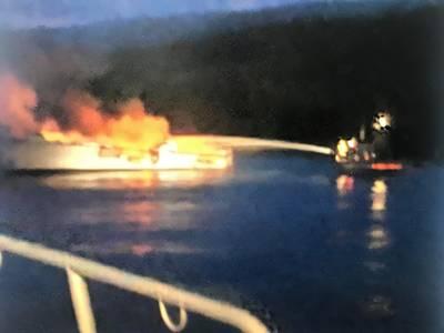 Uma imagem do USCG de agentes locais combatendo o incêndio a bordo da Conceição.