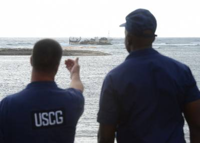 O pessoal da Guarda Costeira dos EUA discute operações futuras para a remoção do produto a bordo da embarcação de pesca comercial Chui Zai Fa No. 1 aterrada a cerca de 300 metros da Leone Bay (foto da Guarda Costeira dos EUA por Tara Molle)