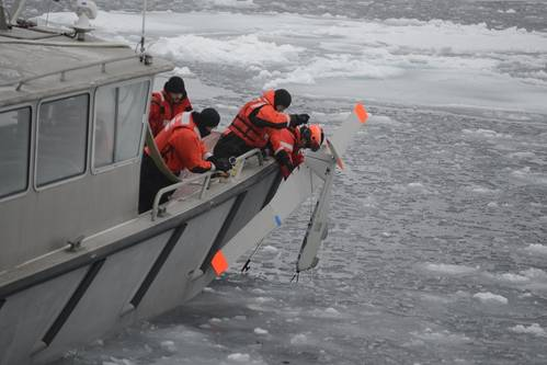 Coast Guard Cutter Healy small boat crew members retrieve a National Oceanic and Atmospheric Administration small unmanned aircraft system after it landed in icy water. The SUAS was used to identify simulated spilled oil so that deployable recovery systems could be utilized. (U.S. Coast Guard photo by Petty Officer 3rd Class Grant DeVuyst)
