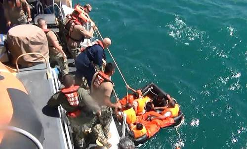 Coast Guardsmen from U.S. Coast Guard Cutter Maui rescue five Iranian mariners after they were found adrift in a life raft. U.S. Navy video capture.