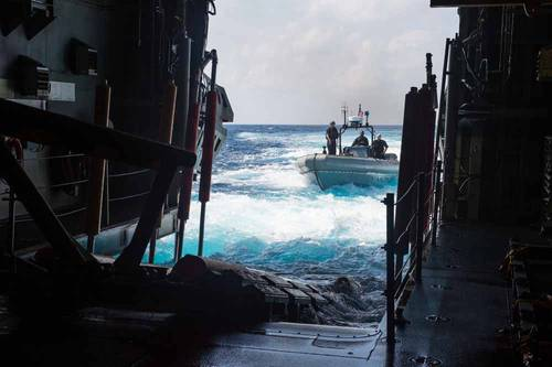 An 11 meter rigid hull inflatable boat (RHIB) approaches the open stern doors of the water borne mission zone aboard the USS Fort Worth (LCS 3). (U.S. Navy photo by Mass Communication Specialist 2nd Class Antonio Turretto Ramos)
