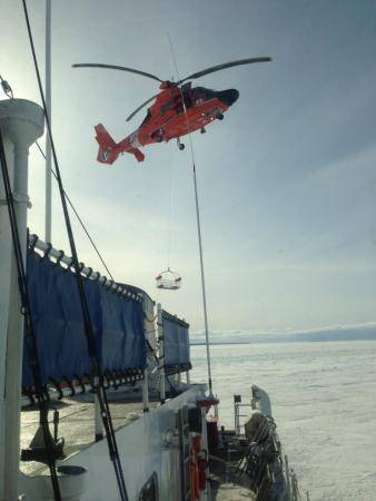 An MH-65C Dolphin helicopter crew from Coast Guard Air Station Traverse City, Mich., conducts hoist training operations with the crew of Coast Guard Cutter Katmai Bay Feb. 5, 2014. (U.S. Coast Guard photo by Seaman James Ash)