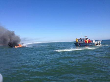 North Sea Fire Department fights a fire aboard a 36-foot cabin cruiser near Shinnecock, N.Y. (U.S. Coast Guard photo by Adam Long)
