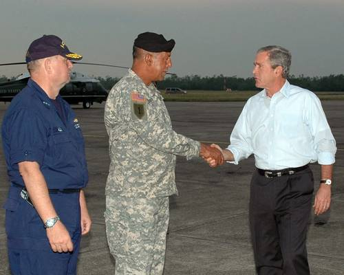 Then President George W. Bush (R) greets Commander, Joint Task Force Katrina, U.S. Army Lt. Gen. Russel Honore, and Director of FEMA Relief Efforts, U.S. Coast Guard Vice Adm. Thad W. Allen (L) as he steps off Air Force One on board Naval Air Station Joint Reserve Base, New Orleans, Oct. 10, 2005. U.S. Navy Photo