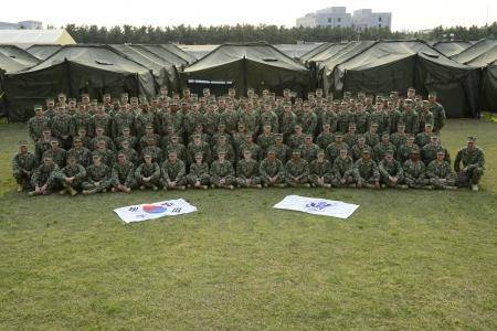 The crew of Port Security Unit (PSU) 313, of Everett, Wash., pose for a unit photo in front of berthing tents at Camp Baldwin. April 28, 2013. This is the first time since 2006 that a Coast Guard PSU has participated in the Korean Theater of Operations (KTO). (U.S. Coast Guard photo by Petty Officer 2nd Class Etta Smith/Released)