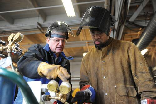 Instructor Mike Rasmussen working with student at the Swan Island Training Center in Portland. (Photo credit: Vigor Industrial)