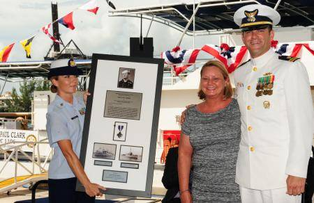 Joanne Kropp, sponsor of Coast Guard Cutter Paul Clark, receives a plaque with the Navy Cross from Lt. W.W. Lloyd Belcher, commanding officer of Paul Clark, during the cutter's commissioning ceremony. U.S. Coast Guard photo by Petty Officer 3rd Class Jon-Paul Rios.