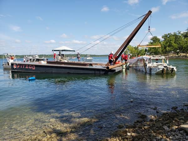 Береговая охрана США наблюдает за удалением Stretch Duck 7 из Rock Rock Lake в Брэнсоне, штат Миссури, 23 июля 2018 года. Миссиори штата Патруль-патруль сгрузил судно, затем кран-барж поднял его на поверхность, прежде чем он был отбуксирован на берег и загружается на планшетный трейлер для транспортировки в безопасное место. (Фото Береговой охраны США Лора Ратлифф)
