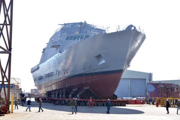 Будущее прибрежное боевое судно USS Indianapolis (LCS 17) перемещается с крытого производственного объекта в Маринетт, штат Висконсин, на пусковые установки в рамках подготовки к его запуску 14 апреля в реку Менменоэ. (Фотография ВМС США, любезно предоставленная Marinette Marine от Val Ihde)