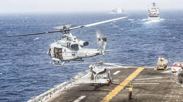 Вертолет «Яд UH-1Y», предназначенный для морской эскадрильи среднего тильтротора (VMM) 163 (11-й усиленный), 11-й морской экспедиционный отряд (MEU), взлетает с палубы десантного десантного корабля USS Boxer (LHD 4) во время проливного транзита. Группа по боевой амфибии Boxer и 11-я MEU развернуты в районе операций 5-го флота США в поддержку военно-морских операций для обеспечения стабильности и безопасности на море в Центральном регионе, соединяющем Средиземное море и Тихий океан через запад