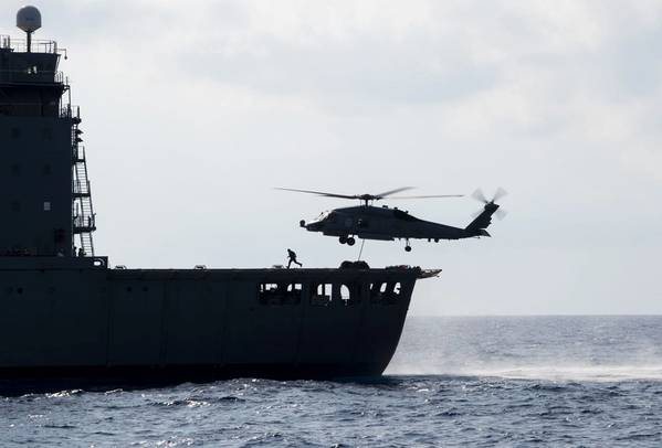 """جنوب الصين (7 مايو ، 2019) طائرة هليكوبتر من طراز MH-60R Sea Hawk تم تخصيصها لـ """"Easyriders"""" من سرب طائرات الهليكوبتر Maritime Strike (HSM) 37 ، مفرزة 1 ، تلتقط منصات نقالة من أسطول القيادة العسكرية للتجديد البحري -AO 200) خلال عملية تجديد في البحر مع مدمرة صواريخ موجهة من طراز Arleigh Burke-USS Preble (DDG 88). تم نشر شركة Preble في منطقة عمليات الأسطول الأمريكي السابع لدعم الأمن والاستقرار في منطقة المحيط الهادئ الهندية. (الصورة البحرية الأمريكية"""