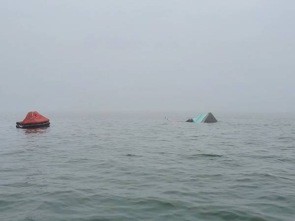 """2020年1月15日,得克萨斯州加尔维斯顿的加尔维斯顿码头附近发生碰撞后,这艘81英尺高的捕鱼船""""帕皮的骄傲""""船尾出现在水线上方,该船的充气救生筏旁边。(美国海岸警卫队加尔维斯顿摄)"""