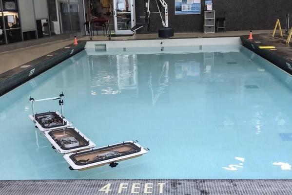 """Die Flotte von Roboterbooten des MIT wurde mit neuen Funktionen zur """"Formänderung"""" aktualisiert, indem sie autonom voneinander getrennt und in verschiedene Konfigurationen zusammengebaut werden, um verschiedene schwimmende Plattformen in den Kanälen von Amsterdam zu bilden. Bei Experimenten in einem Becken haben sich die Boote von einer verbundenen Geraden in ein """"L"""" (hier gezeigt) und andere Formen umgeordnet. Bildnachweis: MIT"""