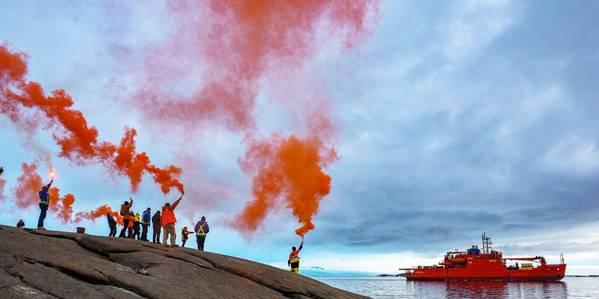 Expedicionistas segurando flares para se despedir da Aurora Australis, à medida que parte da estação de pesquisa Mawson, em 26 de fevereiro de 2020 (Foto: Matt Williams)
