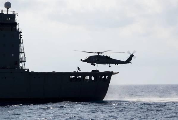 """南中国海(2019年5月7日)MH-60R海鹰直升机被分配到直升机海上打击中队(HSM)37的""""Easyriders"""",支队1,从军事海运司令部舰队补给油船USNS Guadalupe(T)获取托盘-AO 200)在与Arleigh Burke级导弹驱逐舰USS Preble(DDG 88)的海上补给期间。 Preble部署到美国第7舰队运营区,以支持印度洋 - 太平洋地区的安全和稳定。 (美国海军照片"""