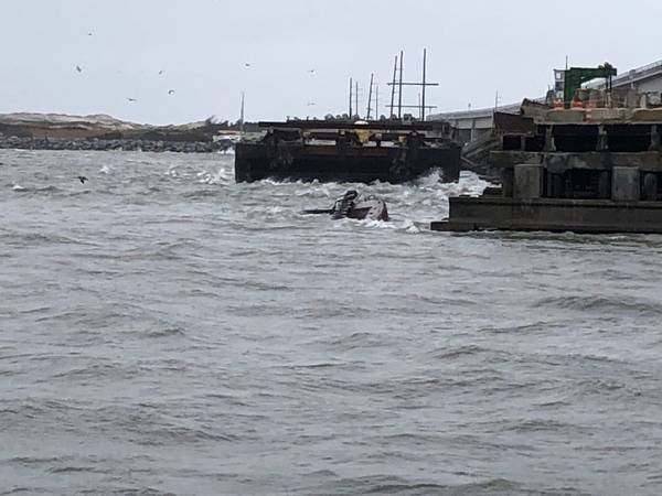 El remolcador semi-sumergido Miss Bonnie se sienta en el agua después de aliarse con el Puente Old Bonner en Oregon Inlet, Carolina del Norte. (Foto de la Guardia Costera de EE. UU., Cortesía de la entrada de Oregon de la Guardia Costera)
