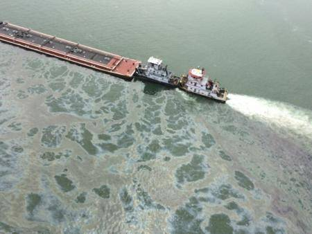 A barge loaded with marine fuel oil sits partially submerged in the Houston Ship Channel, March 22, 2014. The bulk carrier Summer Wind, reported a collision between the Summer Wind and a barge, containing 924,000 gallons of fuel oil, towed by the motor vessel Miss Susan. (USCG photo)