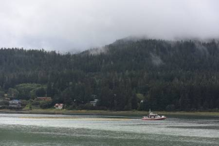 A Coast Guard Station Juneau 45-foot Response Boat-Medium crew tows a section of containment boom up Gastineau Channel in Juneau, Alaska, Sept. 13, 2015. Coast Guard Sector Juneau response personnel deployed with the boat crew to place the boom around a sunken tug. (U.S. Coast Guard photo by Petty Officer 2nd Class Grant DeVuyst)