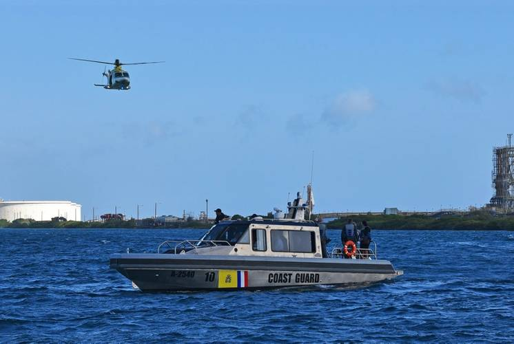A Dutch Caribbean Coast Guard AW139 helicopter flies above a Metal Shark 38 Defiant patrol boat following a commissioning ceremony in Aruba on January 23rd, 2019.