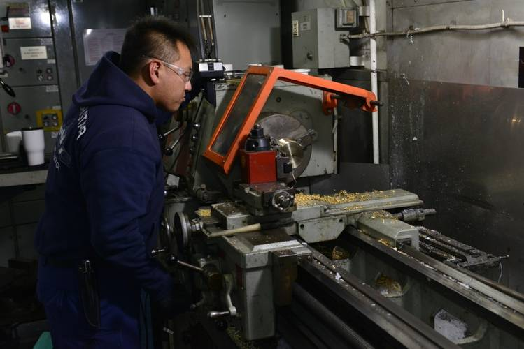 A marine science technician aboard the Coast Guard Cutter Polar Star uses a lathe to fabricate a brass bushing for the ship's propulsion machinery(U.S. Coast Guard photo by Nick Ameen)