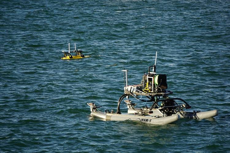A Seabotix ROV is lowered into the water from a WAM-V, with a Z-Boat 1800RP nearby (Photo: Eric Haun)