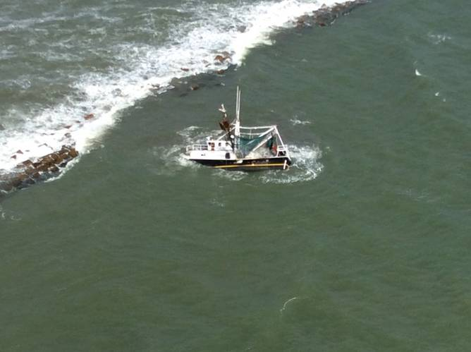 A shrimp boat is grounded on South Galveston Jetty after three fisherman aboard were rescued by the Coast Guard. (U.S. Coast Guard photo by Air Station Houston)