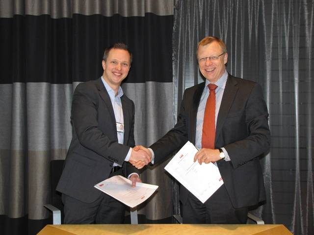 ABB's Mikko Lepisto and NAPA's Juha Heikinheimo shaking hands after signing the cooperation agreement.