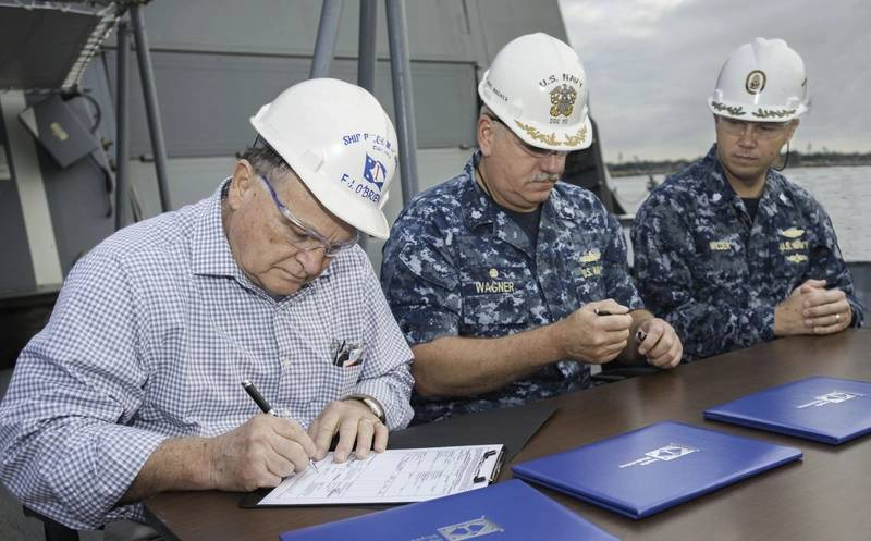 Aegis guided missile destroyer John Finn (DDG 113), named for a Pearl Harbor hero and the Navy's first World War II Medal of Honor recipient, was delivered on the 75th anniversary of the attack on Pearl Harbor, Dec. 7, 2016. Signing the document are, from left, Freddie Joe O'Brien, Ingalls' DDG 113 ship program manager; Navy Cmdr. Micheal Wagner, prospective commanding officer of DDG 113; and Cmdr. Ben Wilder, former Navy DDG 51 program manager's representative. (Photo: Lance Davis/HII)