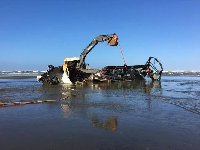 An excavator is attached to the beached fishing vessel Privateer to help stabilize it as salvage experts evaluate the vessel for pollution threat and eventual salvage. (U.S. Coast Guard photo by Bradley Bennett)